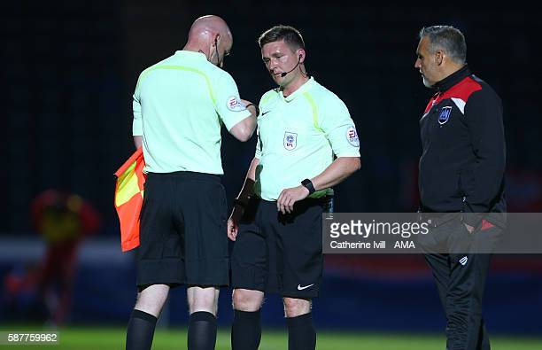 Referee Lee Collins hand the cards over to assistant Marvyn Amphlett who substitutes him during the EFL Cup match between Wycombe Wanderers and...