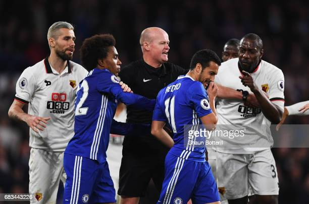 Referee Lee Mason attempts to stop Pedro of Chelsea and Stefano Okaka of Watford from clashing during the Premier League match between Chelsea and...