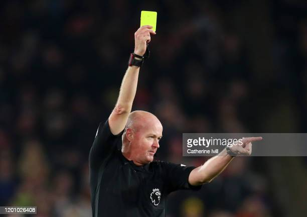 Referee Lee Mason awards a yellow card during the Premier League match between Sheffield United and Manchester City at Bramall Lane on January 21,...