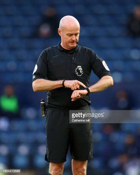 Referee Lee Mason checks his watch during the Premier League match between West Bromwich Albion and Brighton & Hove Albion at The Hawthorns on...