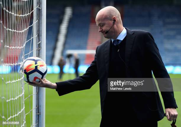 Referee Lee Mason checks the goal line technology during the Premier League match between Huddersfield Town and Manchester United at John Smith's...