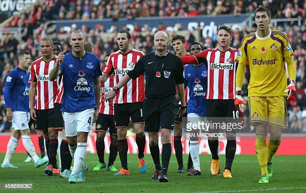 Referee Lee Mason consults with his assistant referee after he gave a penalty after Sunderland's English striker Conor Wickham brought down Evertons...