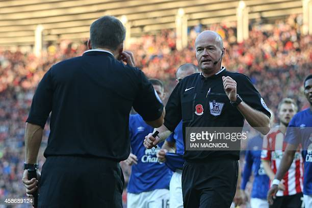 Referee Lee Mason consults with one of his assistants after he gave a penalty after Sunderland's English striker Conor Wickham brought down Evertons...