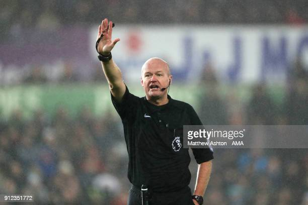 Referee Lee Mason gestures during the Premier League match between Swansea City and Arsenal at Liberty Stadium on January 30 2018 in Swansea Wales