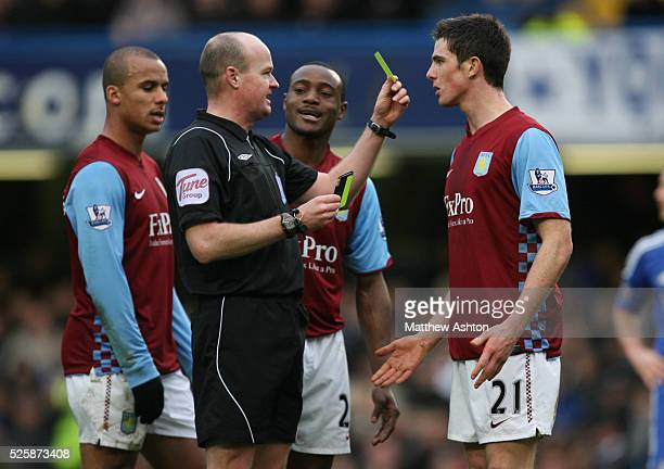 Referee Lee Mason holds up a yellow card to the face of Ciaran Clark of Aston Villa