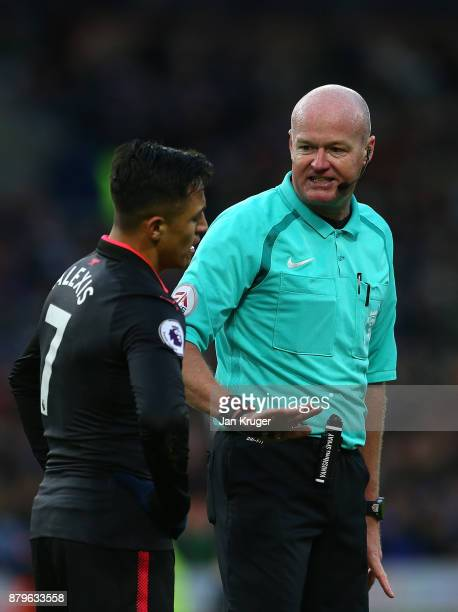 Referee Lee Mason interacts with Alexis Sanchez of Arsenal during the Premier League match between Burnley and Arsenal at Turf Moor on November 26...
