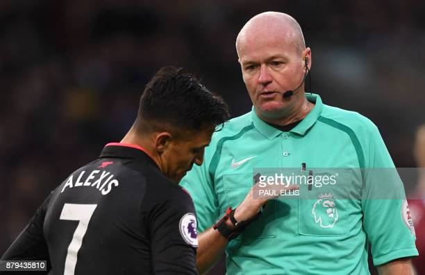 Referee Lee Mason interacts with Arsenal's Chilean striker Alexis Sanchez during the English Premier League football match between Burnley and...
