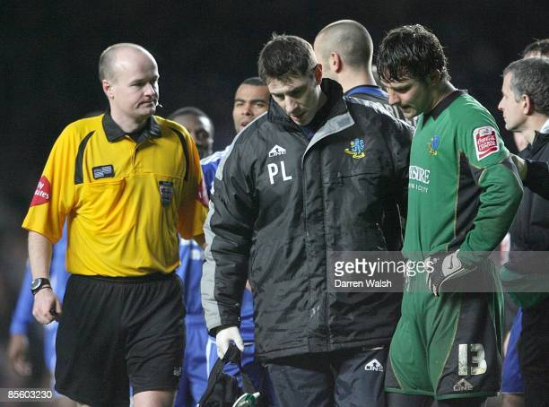 Referee Lee Mason looks on as Macclesfield Town's Physio Paul Lake walks off the pitch with a dejected Tommy Lee after being sent off after a...