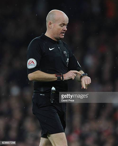 Referee Lee Mason points to his watch during the Premier League match between Arsenal and Stoke City at Emirates Stadium on December 10 2016 in...