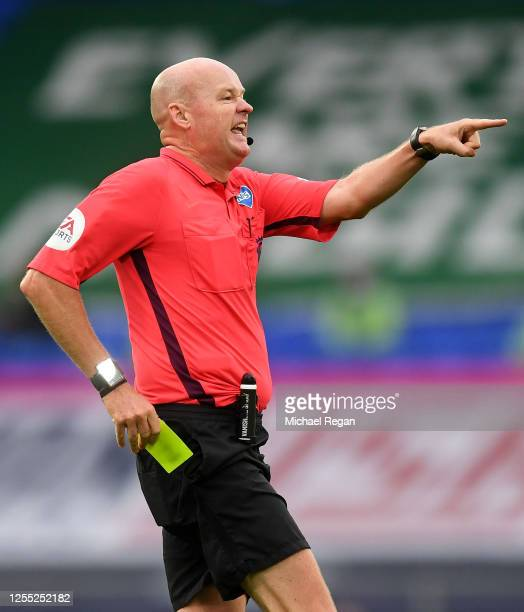 Referee Lee Mason reaches for his yellow card during the Premier League match between Everton FC and Southampton FC at Goodison Park on July 09 2020...