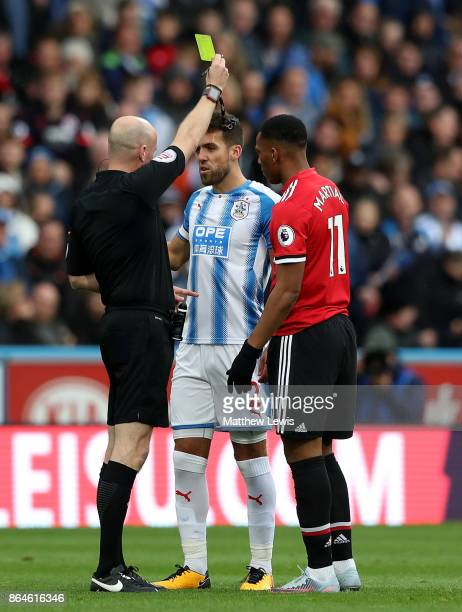 Referee Lee Mason shows a yellow card as Tommy Smith of Huddersfield Town and Anthony Martial of Manchester United look on during the Premier League...