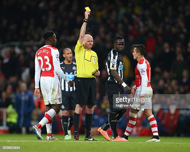 Referee Lee Mason shows a yellow card to Cheik Ismael Tiote of Newcastle United