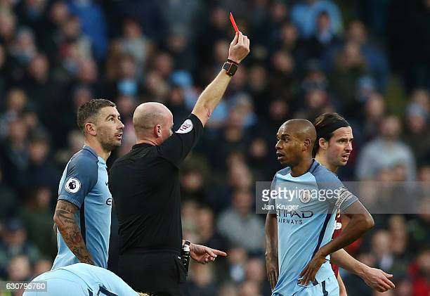 Referee Lee Mason shows the red card to Fernandinho of Manchester City after his challenge on Johann Gudmundsson of Burnley during the Premier League...