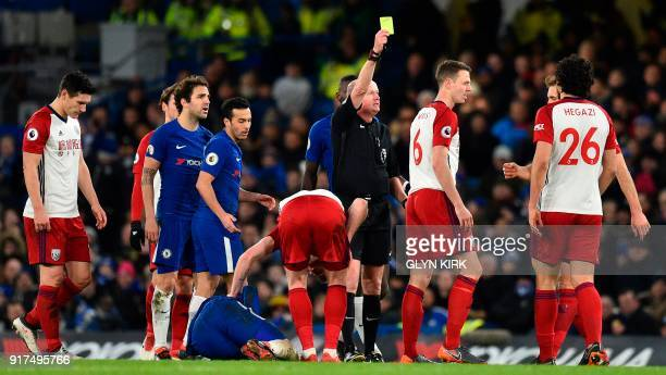 Referee Lee Mason shows West Bromwich Albion's Northern Irish defender Jonny Evans a yellow card for a foul on Chelsea's French attacker Olivier...