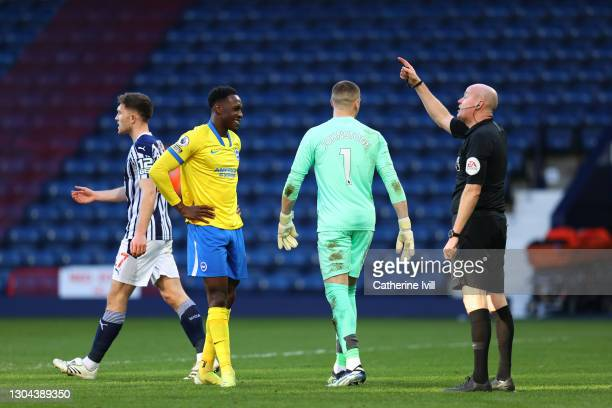 Referee Lee Mason speaks with Danny Welbeck of Brighton and Hove Albion as he reacts after missing a penalty during the Premier League match between...