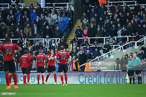 Referee Lee Mason talks to his assistant about Cheick Tiote's disallowed goal in the first half during the Barclays Premier League match between...