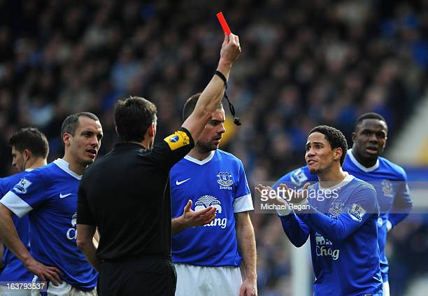Referee Lee Probert shows a red card to Steven Pienaar of Everton during the Barclays Premier League match between Everton and Manchester City at...