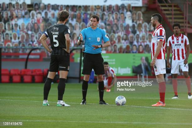 Referee Leigh Doughty performs the coin toss watched by Rival Captains Charlie Goode of Northampton Town and Ben Tozer of Cheltenham Town during the...