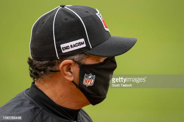 """Referee looks on while wearing a logo on his hat reading """"End Racism"""" before the game between the Washington Football Team and the Dallas Cowboys at..."""