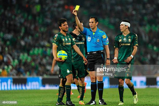 Referee Luis Enrique Santander shows a yellow card to Osvaldo Alanis of Santos during a match between Santos Laguna and Atlas as part of 7th round...