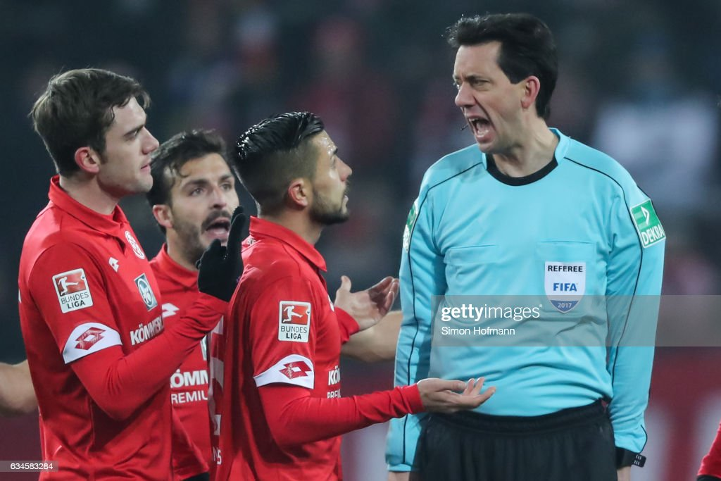 Referee Manuel Graefe argues with tem mates of Mainz during the Bundesliga match between 1. FSV Mainz 05 and FC Augsburg at Opel Arena on February 10, 2017 in Mainz, Germany.