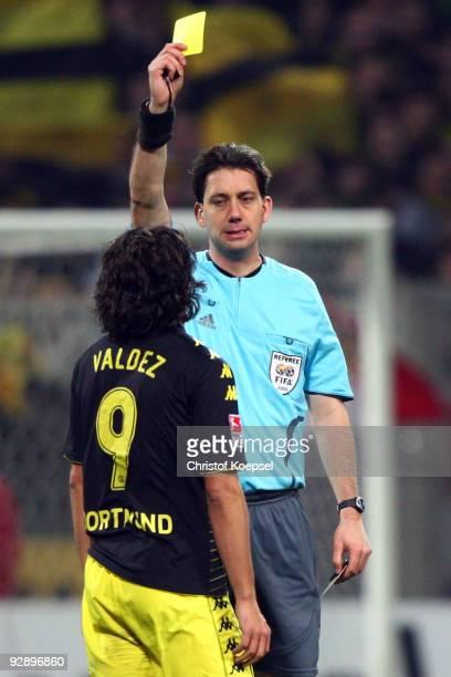 Referee Manuel Graefe shows Nelson Valdez of Dortmund the yellow card during the Bundesliga match between SV Werder Bremen and Borussia Dortmund at...
