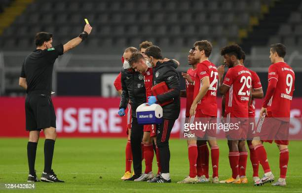 Referee Manuel Graefe shows the yellow card to injured Joshua Kimmich of Muenchen during the Bundesliga match between Borussia Dortmund and FC Bayern...