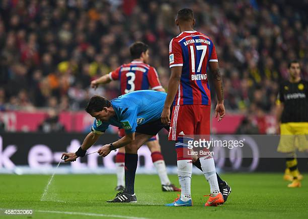 Referee Manuel Gräfe uses vanishing spray during the Bundesliga match between FC Bayern Muenchen and Borussia Dortmund at Allianz Arena on November...