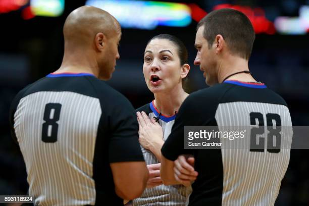 Referee Marc Davis referee Lauren Holtkamp and referee Kevin Scott discuss a call during the second half of a NBA game between the Sacramento Kings...