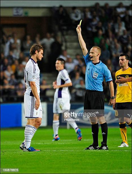 Referee Marcin Borski shows a yellow card to Guillaume Gillet of RSC Anderlecht during the third qualifying round of the UEFA Champions League return...