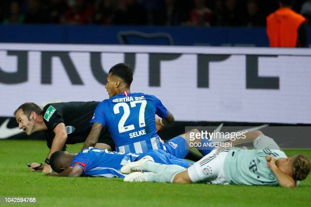 Referee Marco Fritz ends up on the floor with the players after being caught up in a tackle during the German first division Bundesliga football...