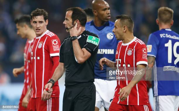 Referee Marco Fritz listens to the video assistant referee on his headset during the Bundesliga match between FC Schalke 04 and FC Bayern Muenchen at...
