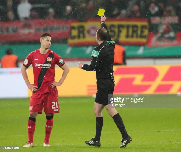 Referee Marco Fritz shows a yellow card to Dominik Kohr of Leverkusen during the DFB Cup match between Bayer Leverkusen and Werder Bremen at BayArena...
