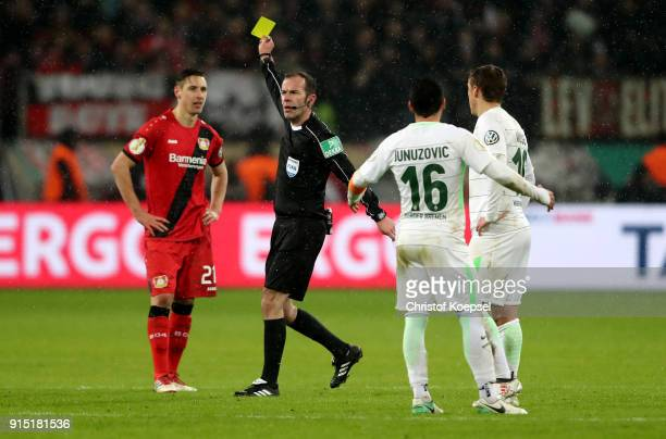 Referee Marco Fritz shows Dominik Kohr of Leverkusen a yellow card during the DFB Cup quarter final match between Bayer Leverkusen and Werder Bermen...