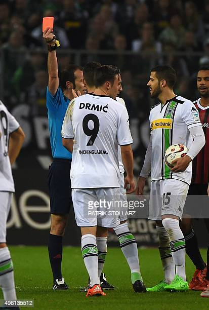 Referee Marco Fritz shows the red card to Moenchengladbach's Swiss midfielder Granit Xhaka next to Moenchengladbach's Spanish defender Alvaro...