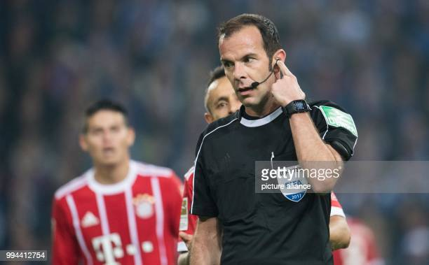 Referee Marco Fritz speaking to his video assistant on his headset during the German Bundesliga soccer match between FC Schalke 04 and Bayern Munich...