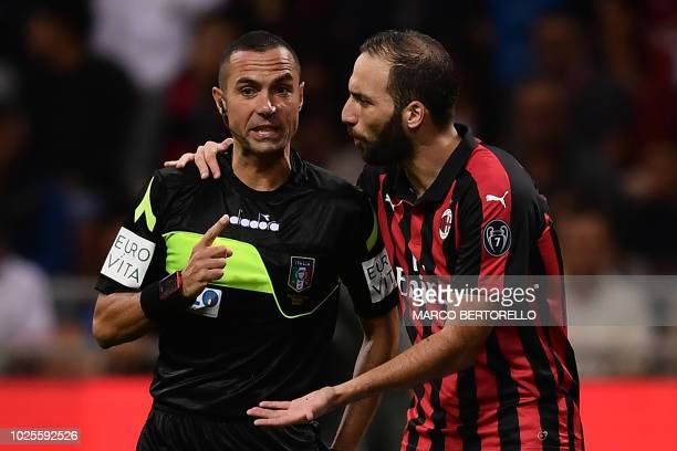 Referee Marco Guida argues with AC Milan's Argentinian forward Gonzalo Higuain during the Italian Serie A football match AC Milan vs Roma on August...