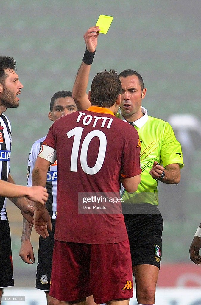 Referee Marco Guida (R) shows a yellow card to Francesco Totti of AS Roma during the Serie A match between Udinese Calcio and AS Roma at Stadio Friuli on March 9, 2013 in Udine, Italy.