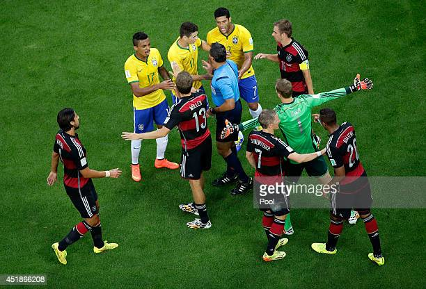 Referee Marco Rodriguez restores order after a challenge during the 2014 FIFA World Cup Brazil Semi Final match between Brazil and Germany at Estadio...