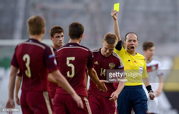 Referee Marius Avram shows a yellow card to Artem Selyukov of Russia U17 during the UEFA European Under17 Championship Semi Final match between...