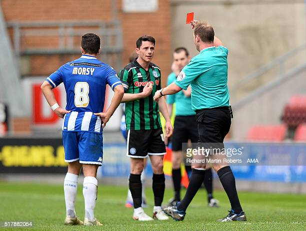 Referee Mark Brown shows a red card to Ian Henderson of Rochdale during the Sky Bet Football League One match between Wigan Athletic and Rochdale at...