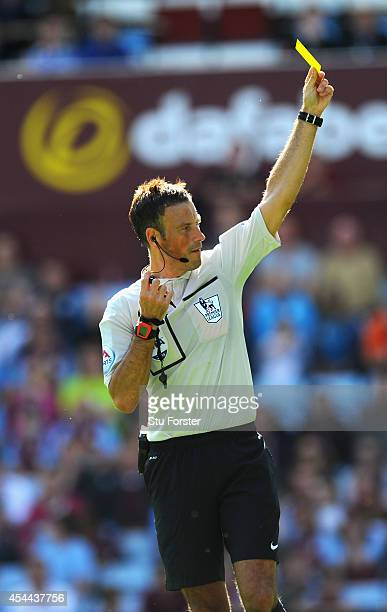 Referee Mark Clattenburg brandishes a yellow card to Hull City player Stephen Quinn during the Barclays Premier League match between Aston Villa and...
