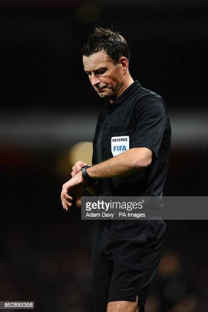 Referee Mark Clattenburg checks his watch