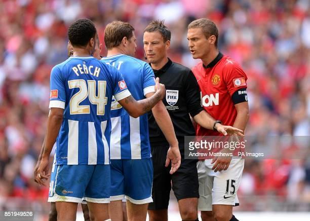 Referee Mark Clattenburg holds back Manchester United's Nemanja Vidic and Wigan Athletic's Grant Holt