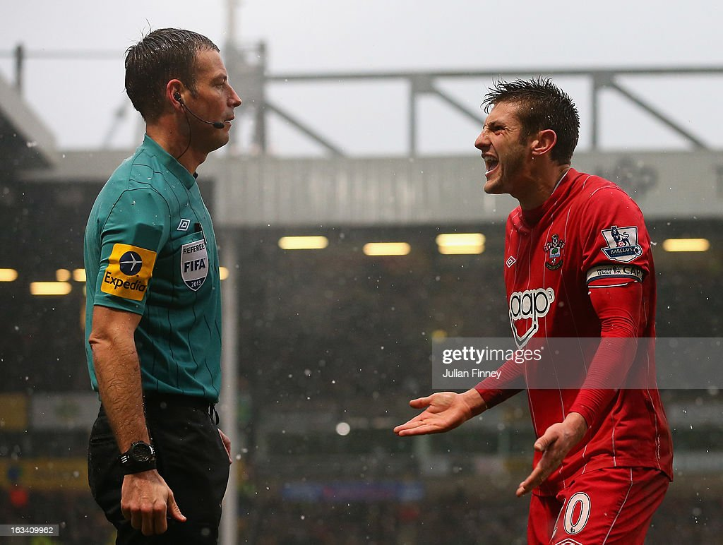 Referee, Mark Clattenburg looks on as Adam Lallana of Southampton complains during the Barclays Premier League match between Norwich City and Southampton at Carrow Road on March 9, 2013 in Norwich, England.
