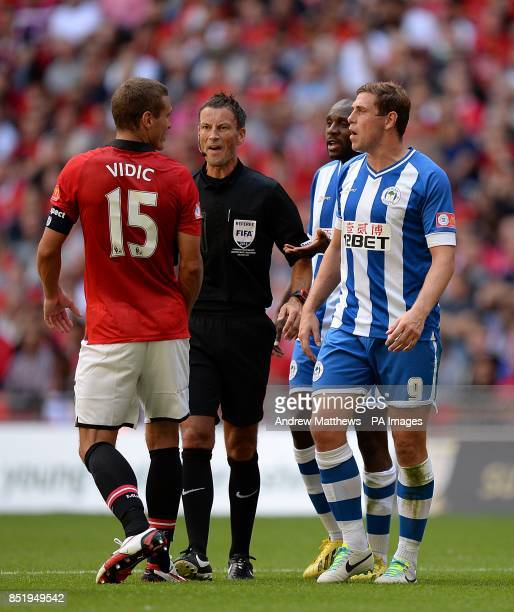 Referee Mark Clattenburg looks on as Manchester United's Nemanja Vidic and Wigan Athletic's Grant Holt confront each other