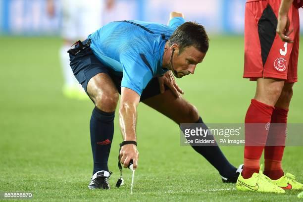 Referee Mark Clattenburg marks a free kick with vanishing spray