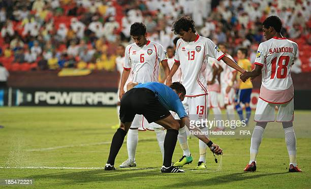 Referee Mark Clattenburg of England uses a spray to mark out the defensive line for a freekick during the FIFA U17 World Cup UAE 2013 Group A match...