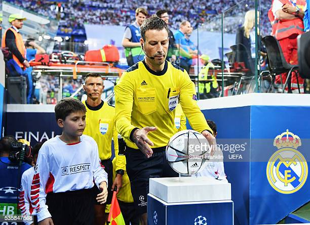 Referee Mark Clattenburg picks up the official match ball during the UEFA Champions League Final match between Real Madrid and Club Atletico de...