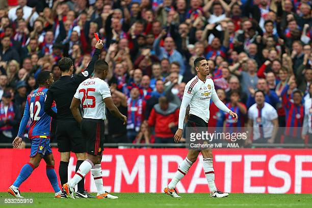 Referee Mark Clattenburg shows a red card to Chris Smalling of Manchester United during The Emirates FA Cup final match between Manchester United and...